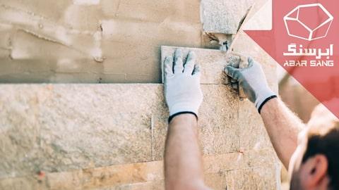 تصویر فردی در حال نصب سنگ در نمای ساختمان