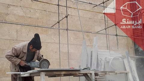 تصویر فردی در حال برش سنگ تراورتن در نمای ساختمان