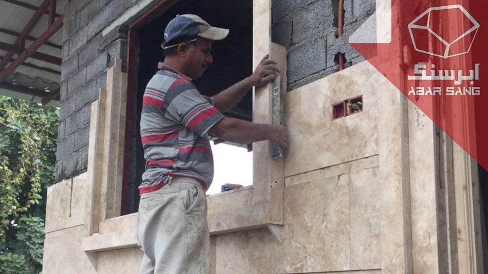 تصویر فردی در حال نصب سنگ تراورتن در نمای ساختمان